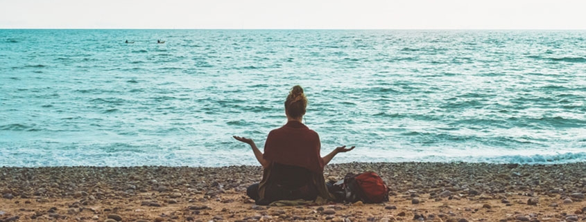 Achtsamkeit und Ruhe: Eine Frau meditiert am Strand