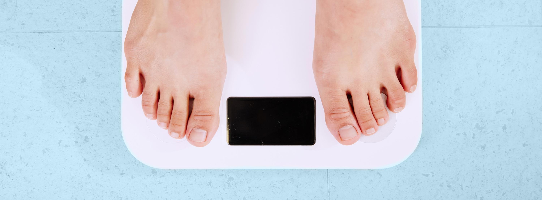 Mensch steht auf der Waage: Gewichtsreduktion und Abnehmen