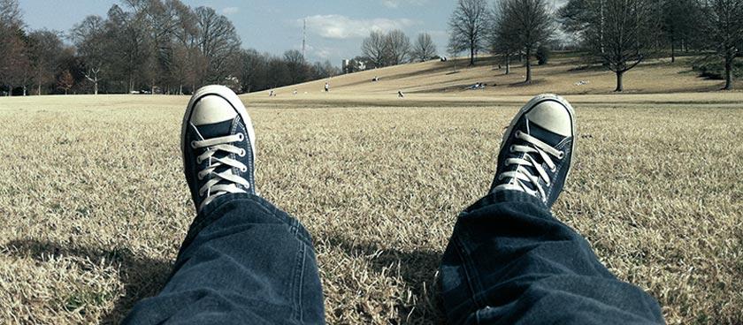 Mann liegt im Gras. Um Effizienzblockaden aufzulösen, muss er mithilfe von Coaching aktiv werden.