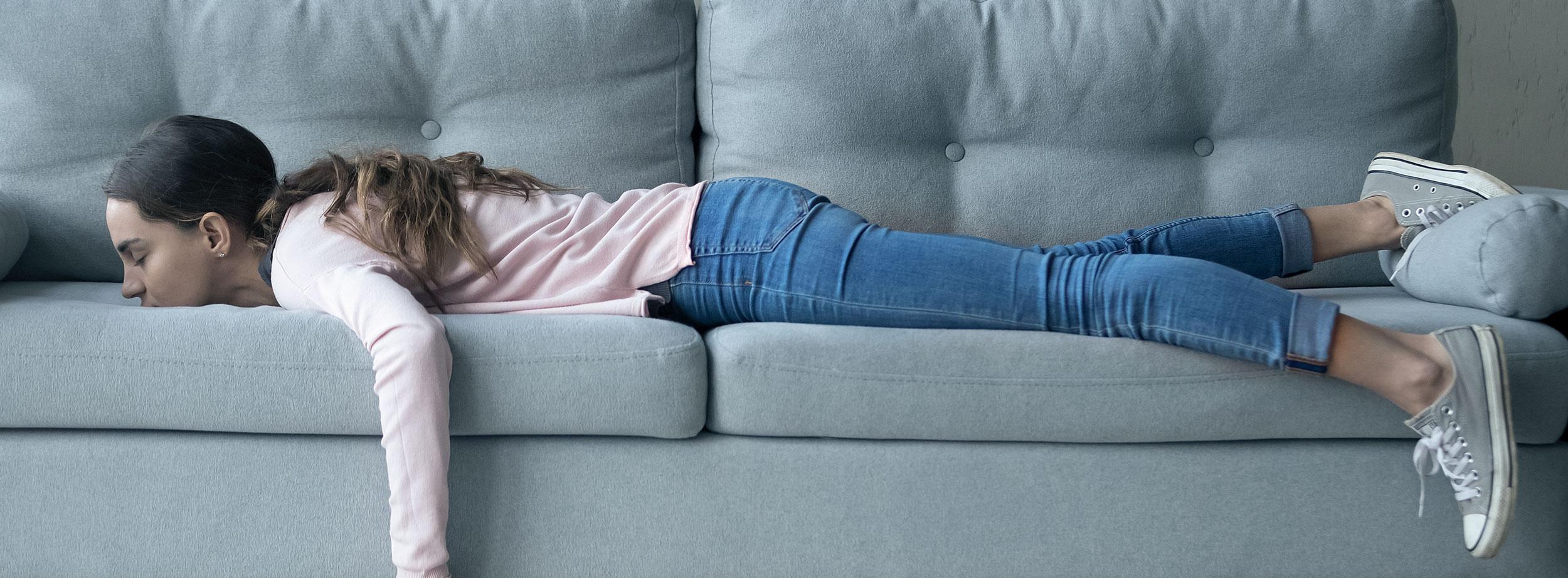 Frau liegt resigniert auf dem Sofa und leidet unter Aufschieberitis