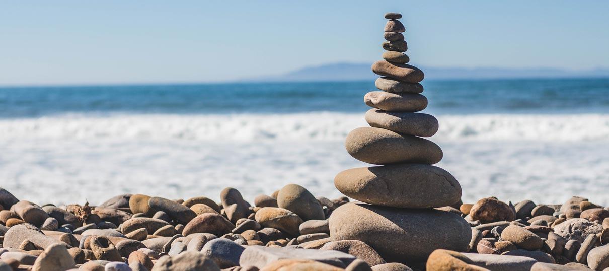 Steinstapel am Meer: mit unserem Behandlungskonzept für Burnout bringen wir Sie wieder in Balance
