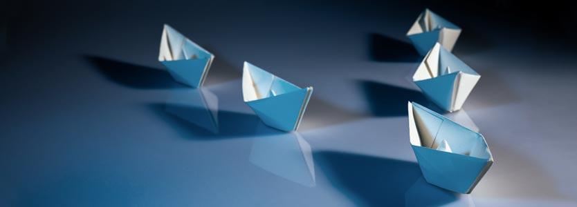 Papierschiffe mit einem Boot in Führung: Business Coaching für Führungskräfte