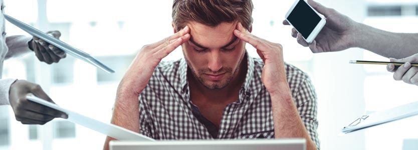 Stress im Büro: Mann hält seinen Kopf in den Händen