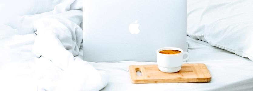 Laptop und Kaffeetasse auf dem Bett: über das Coaching für eine bessere Work-Life-Balance