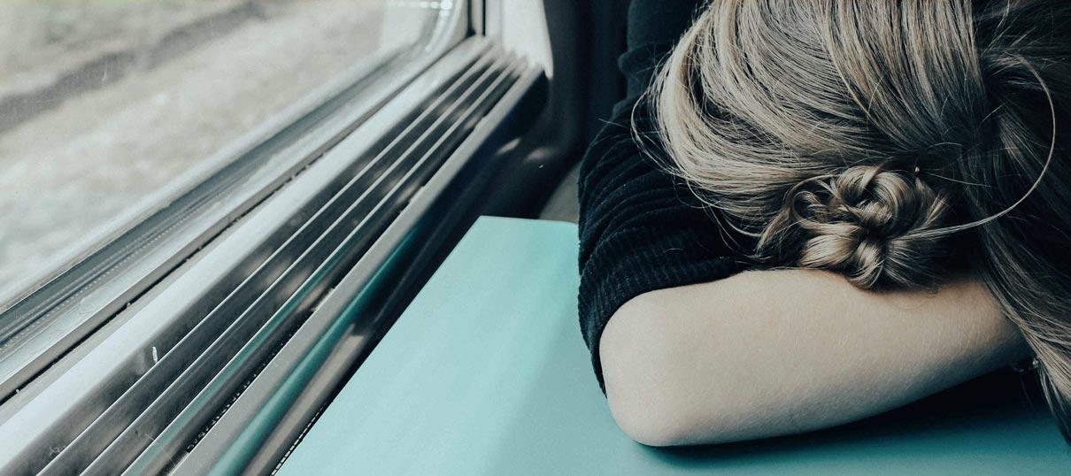Vom Burnout betroffene Frau legt ihren Kopf auf den Tisch und ist erschöpft