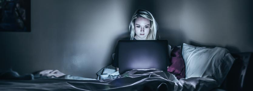 Frau sitzt nachts mit dem Laptop im Bett. Diese Form von schlechter Schlafhygiene kann zu Schlafstörungen führen.