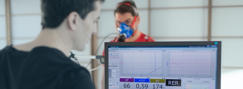 Spiroergometrie im Detail erklärt: Dr. Daniel Holzinger schaut sich die Ergebnisse des Probanden an