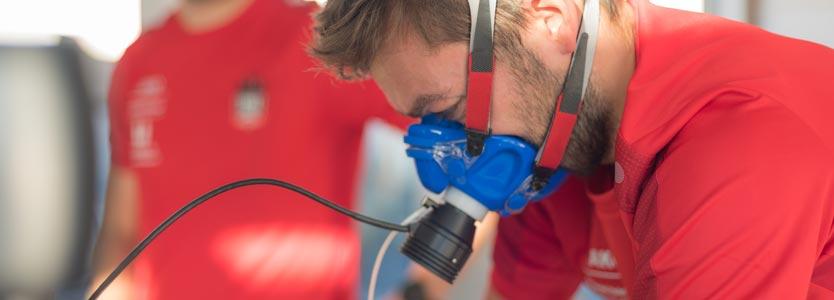 Spiroergometrie im Detail erklärt: die Atemgase des gezeigten Sportlers werden analysiert