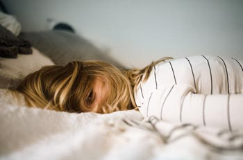 Frau liegt mit dem Gesicht nach unten auf dem Bett und wünscht sich eine besser Work-Life-Balance