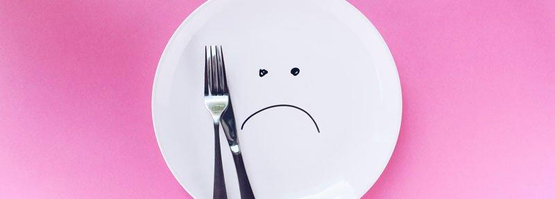 Leerer Telle mit aufgemaltem unglücklichen Gesicht: warum ist Gewichtsreduktion und Abnehmen so schwer?