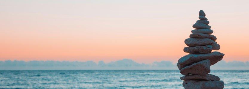 Aufeinander gestapelte Steine am Meer: Gewichtsreduktion und Abnehmen gelingt, wenn Körper und Geist im Gleichgewicht sind